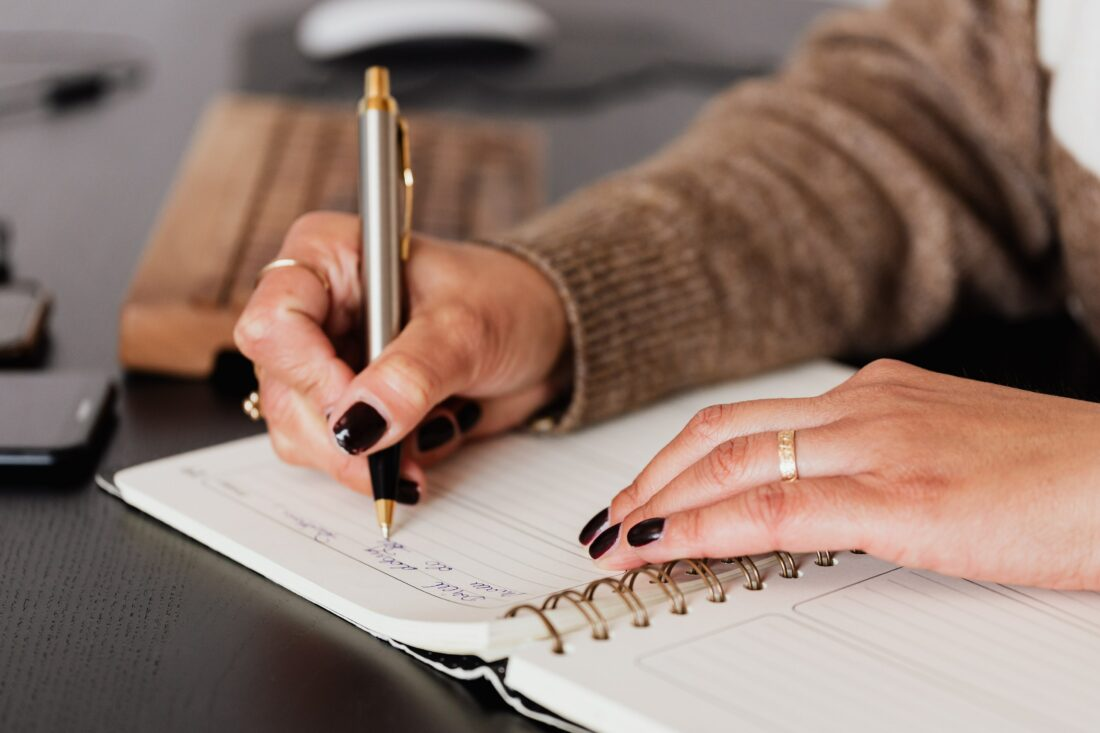 Foto von einer jungen Frau beim Notizen machen